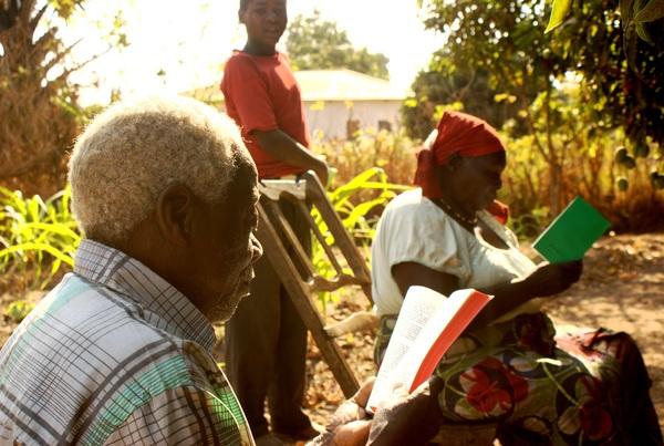Baba and Mayu reading the Sukuma songbook and New Testament