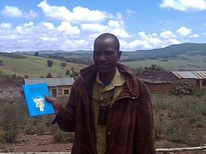 Malila Pastor holding the gospel of Mark in Kimalila