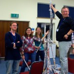 Team with newspaper tower